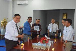 Yosep Ola SH MSi, saat menyerahkan cinderamata kepada Rektor Untad (Foto Taqyuddin Bakri)